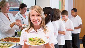 female student in lunch line holding plate of food